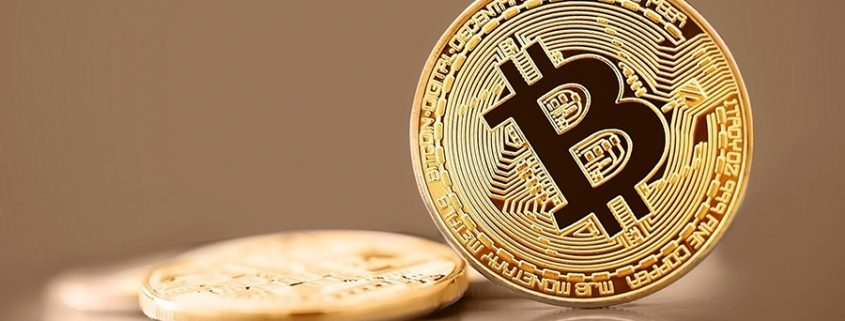 Gold bitcoin on gold background.
