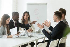 Desacuerdo entre dos personas en una reunión grupal